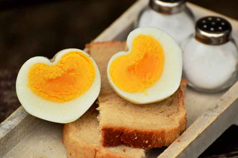 boiled egg on top on bread beside salt shaker